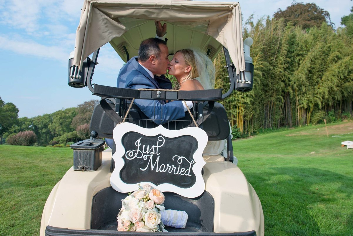 Bride and groom kissing on just married golf cart at Huntington Crescent Club