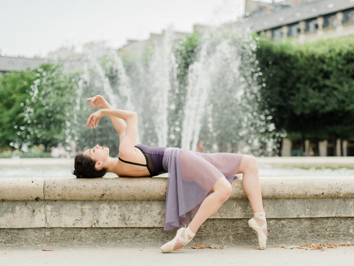 ballerina in purple skirt in front of a fountain