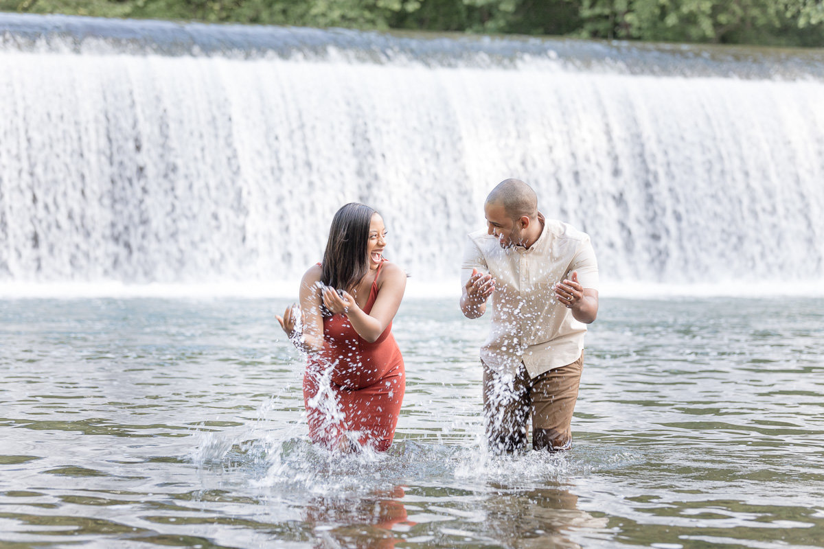 couple splashes water at their maternity photo session