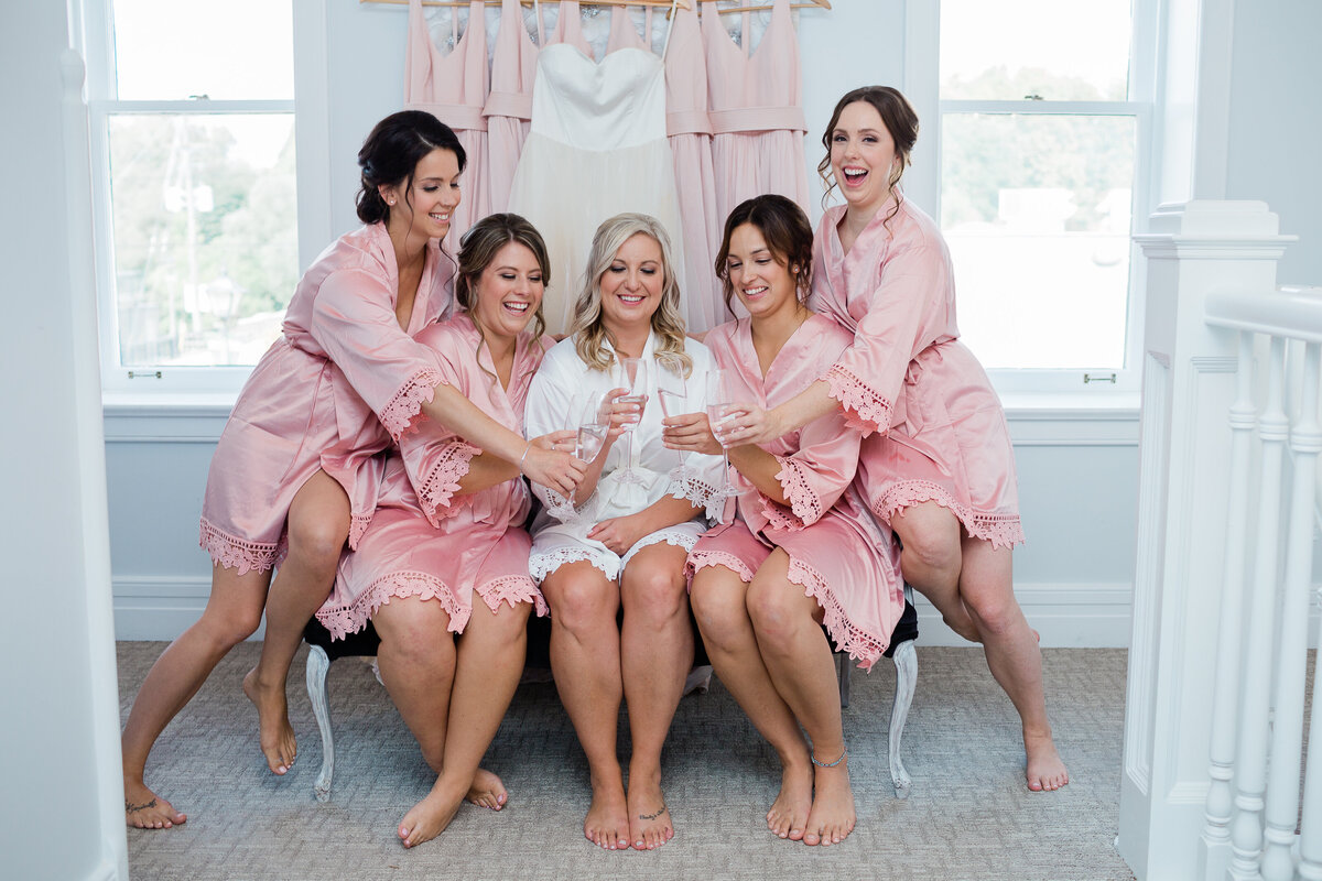 bride and bridesmaids laughing and drinking champaign