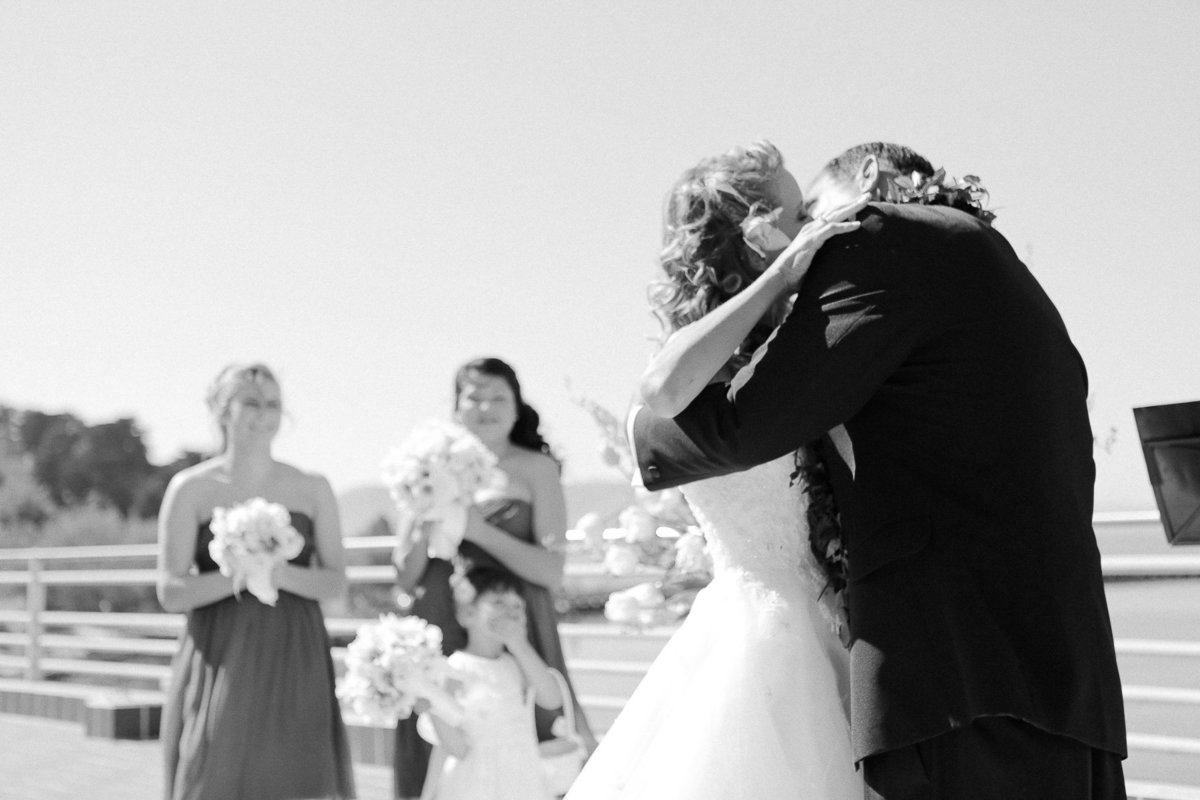 Outdoor wedding kiss during a ceremony at the Maritime Museum in San Francisco.