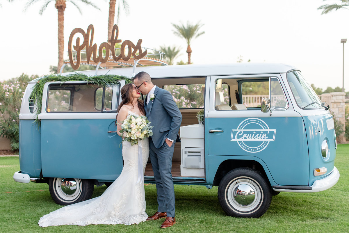 bride and groom touching noses in front of photo booth bus