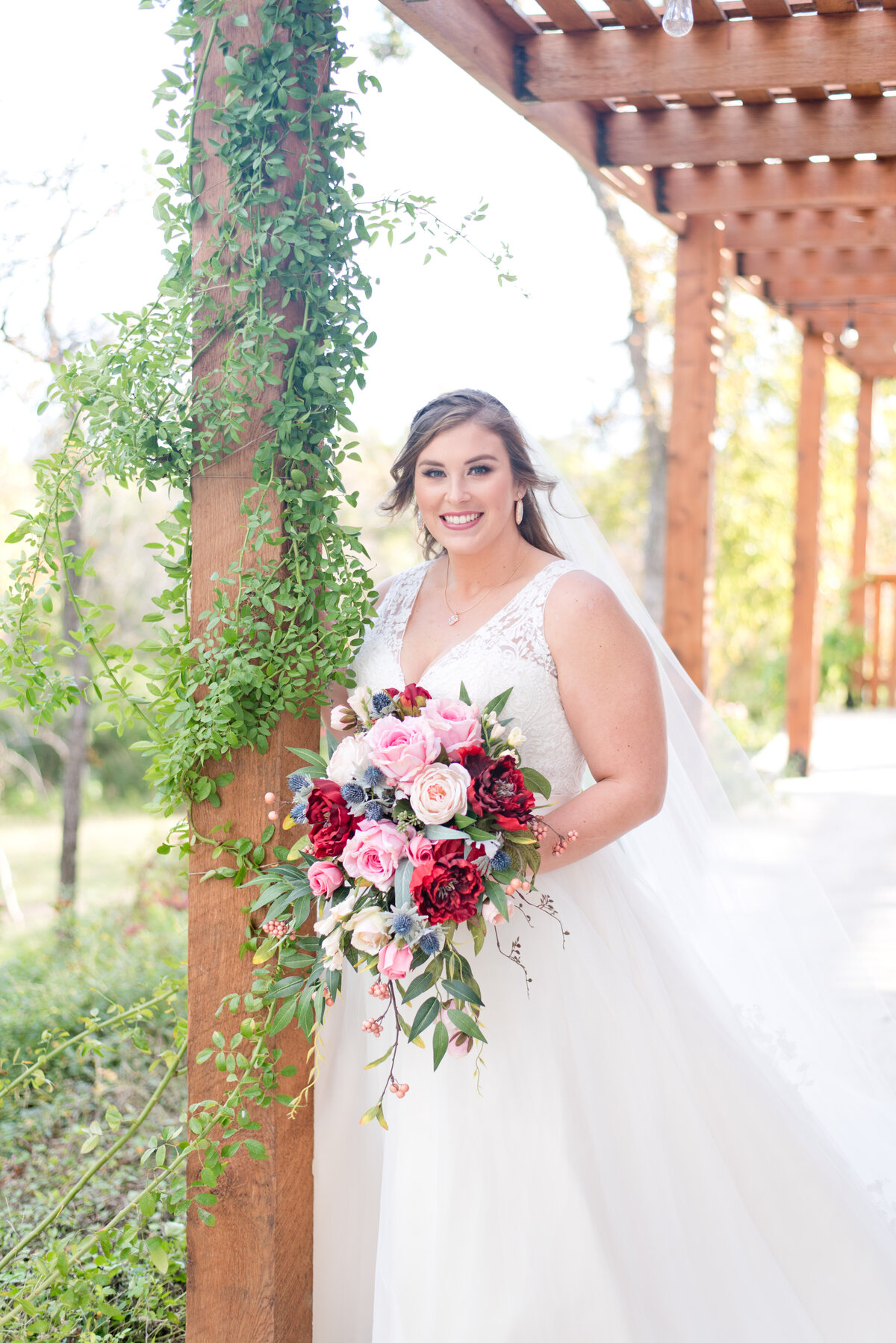Bride standing outside Fort Worth wedding venue with bold colorful flower bouquet