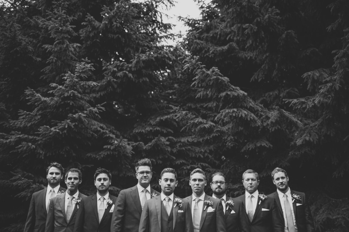 groomsmen lined up in the woods. the bridal party in formation