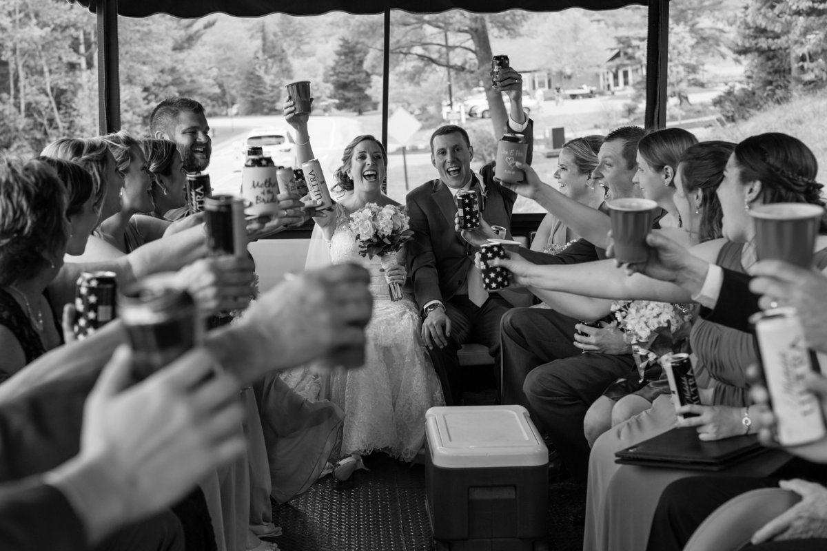 The bride and groom share a toast with their wedding party on the trolley in Waterville Valley Resort New Hampshire