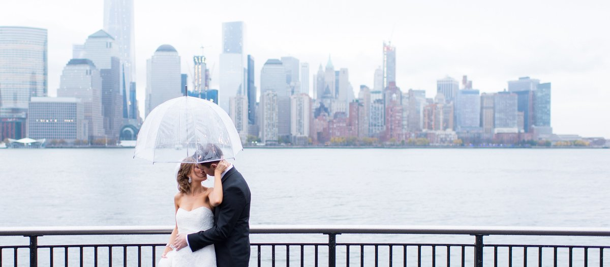 Bride and Groom Kissing under Clear Umbrella and overlooking New York City at Liberty Park in Jersey City, New Jersey Photo