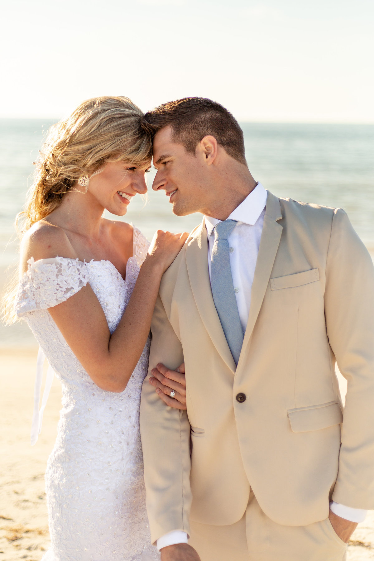 Bride and groom look at each other at their beach wedding in Dunedin, Florida with her in a white wedding dress and him in his tan suit showing off her engagement ring