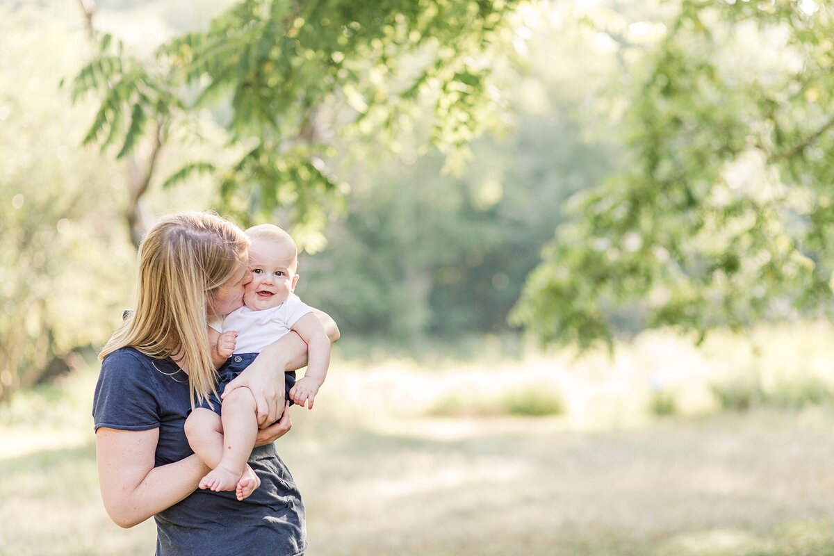 Mother kisses baby during family photo session at Barber Reservation, Sherborn Massachusetts