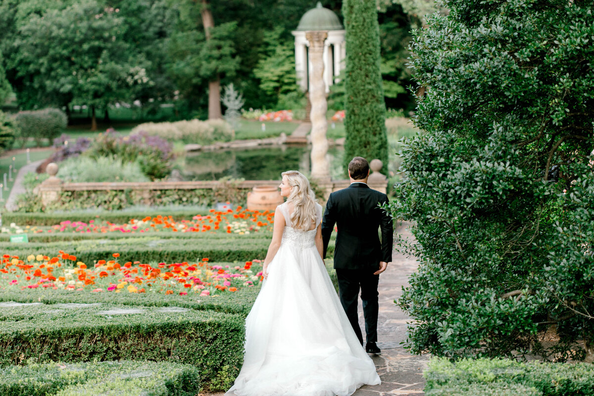 Bride and Groom walking in a garden at Phillbrook Museum in Oklahoma