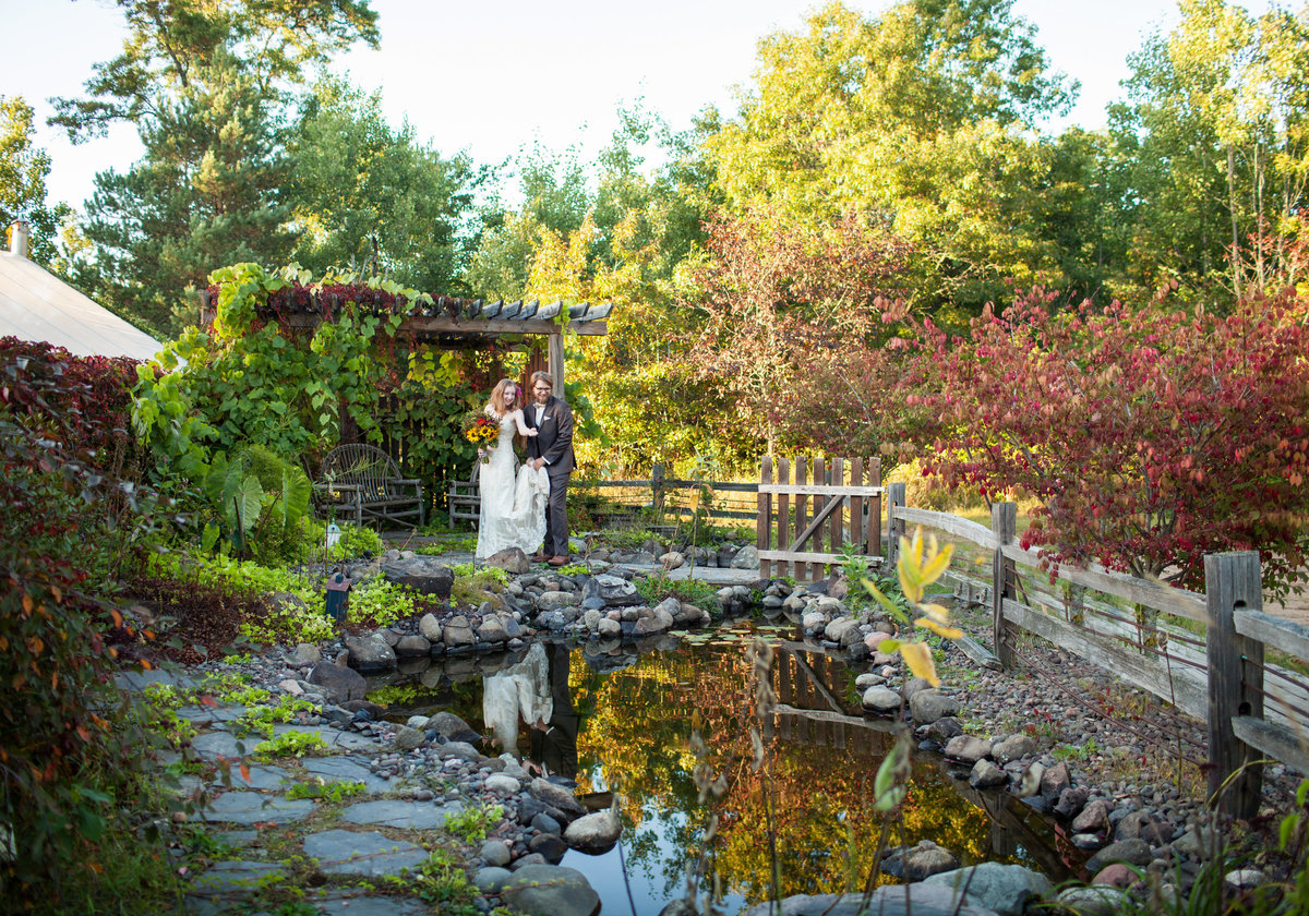 Wedding couple standing by an arbor and a pond.