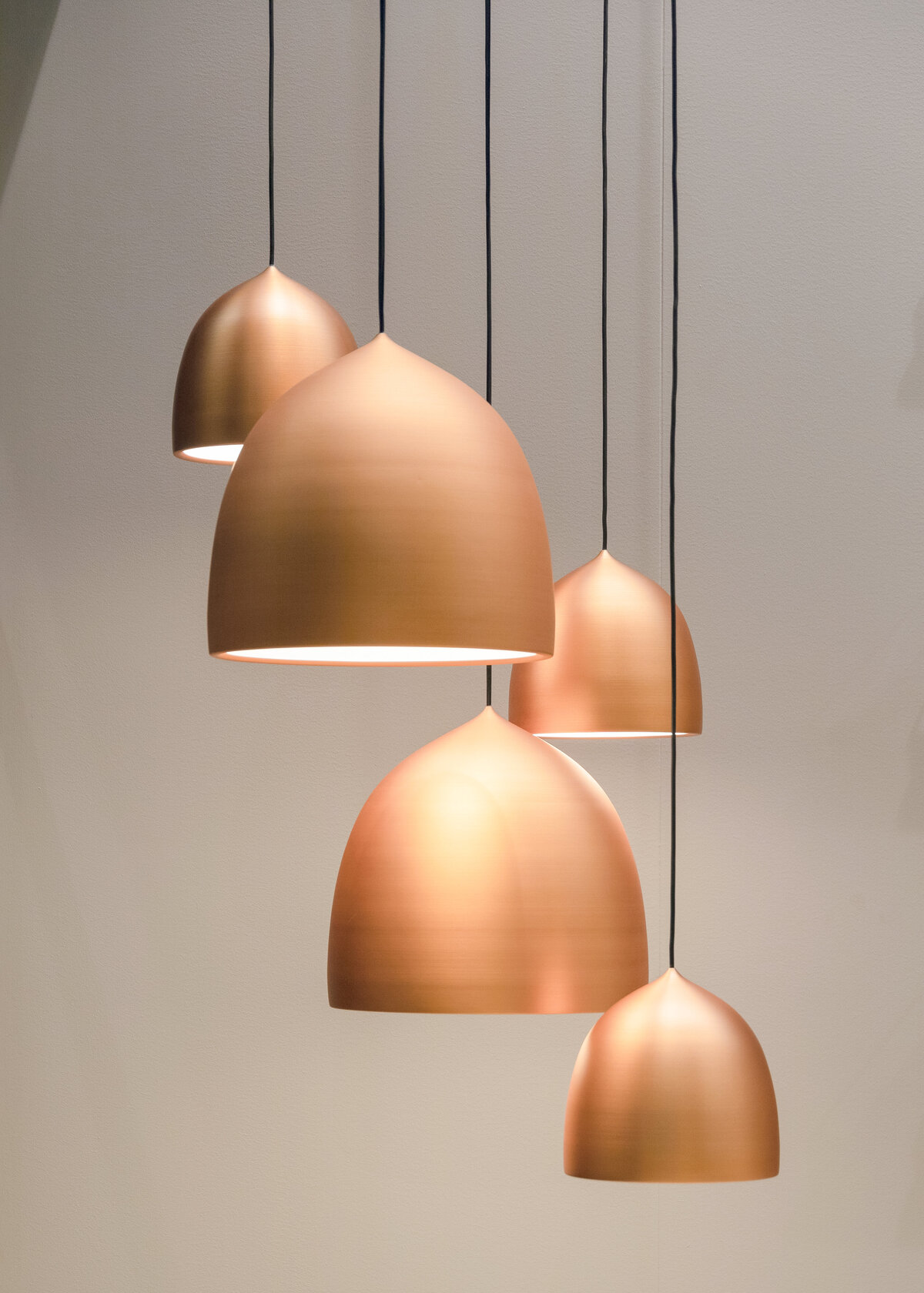An assortment of copper gold pendant lights hang in a collection as interior decor.