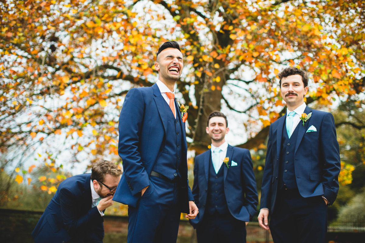groomsmen in blue suits and orange ties laughing