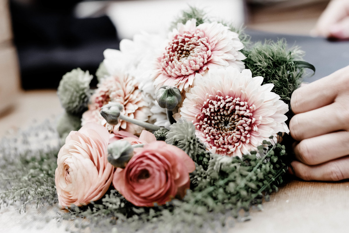 a classic bouquet featuring gerrondo daisies, ranunculus, pennycress and pompoms in shades of green, peach and dusty rose