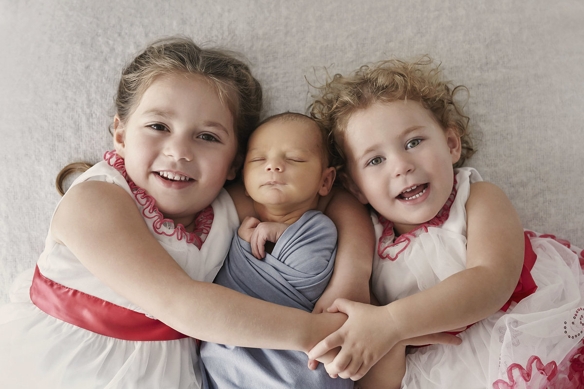 Sisters in matching dresses cuddling up to newborn sleeping baby in the middle smiling and looking at camera