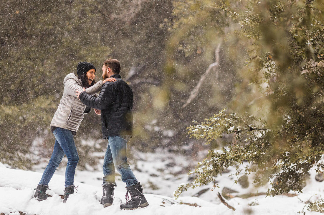 Couple playfully embraces during their snowy engagement session in Forest Falls, Ca.