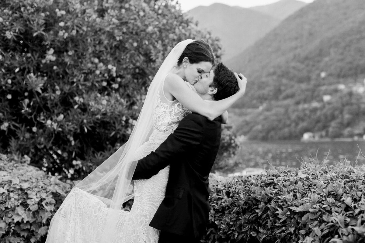 Bride in white lace bridal dress and veil kissing groom by Lake Como Wedding Italy