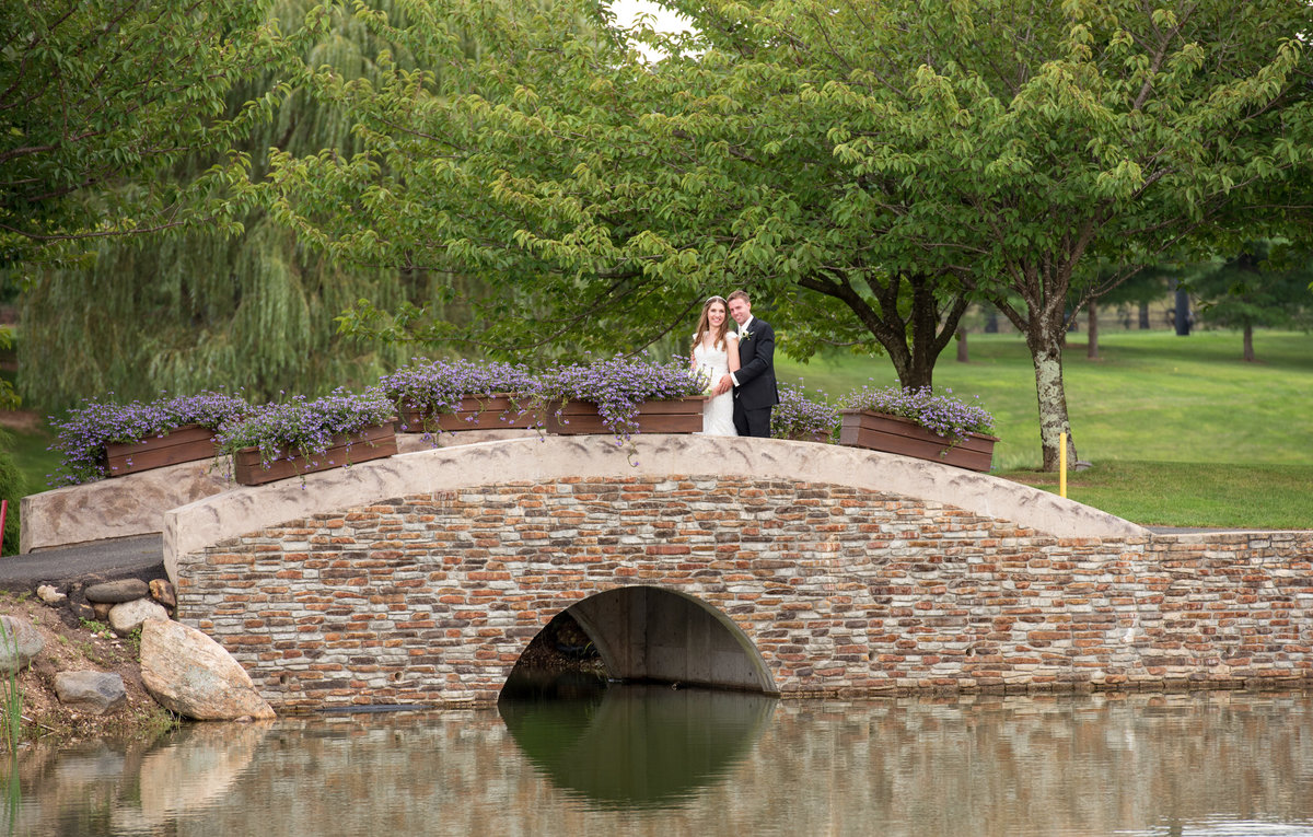 bride and groom standing on bridge at Willow Creek Golf and Country Club