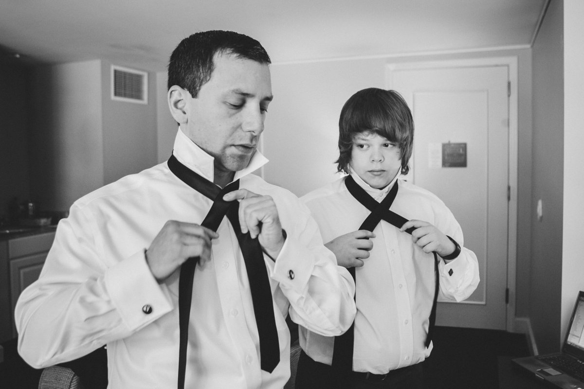 Boy watching dad put on tie