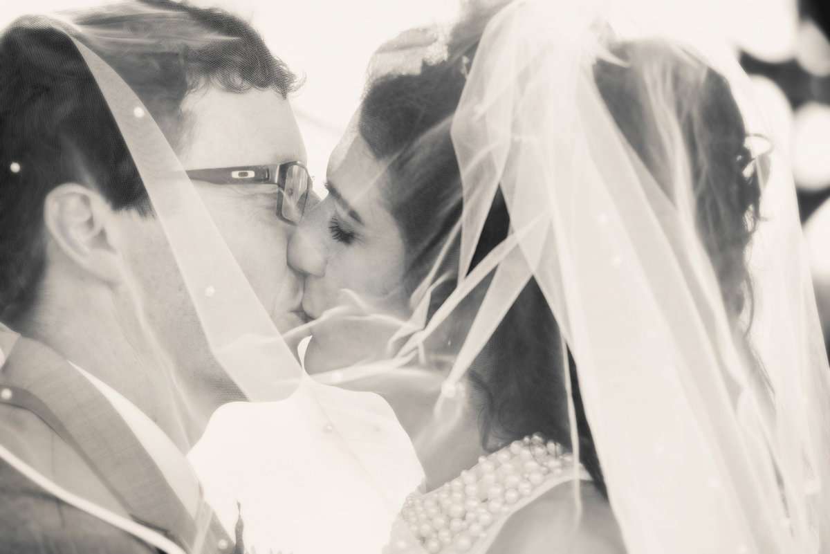 bride and groom kissing under veil hilton garden inn yuma az