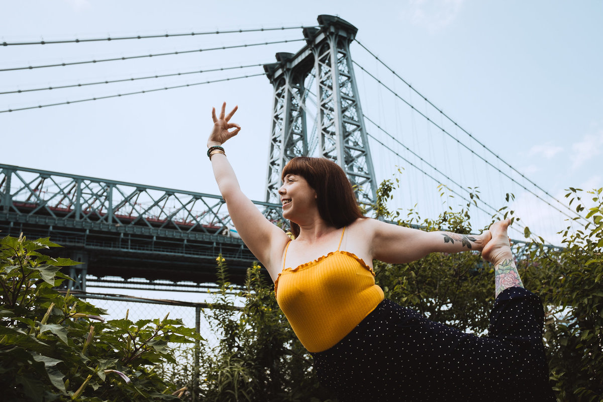 yoga teacher in dancer's pose by brooklyn bridge