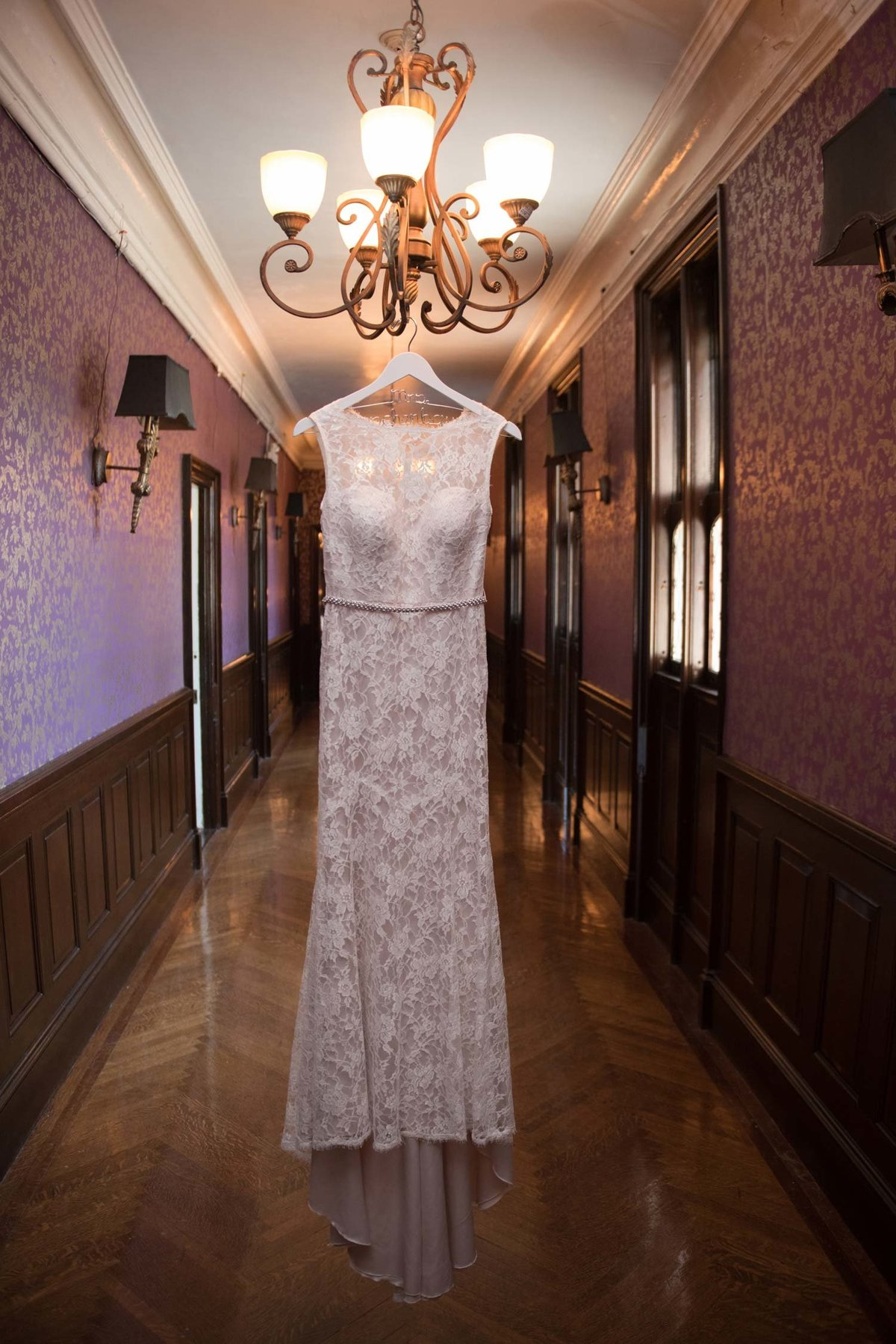 Bride's wedding dress hanging on a chandelier at Hempstead House