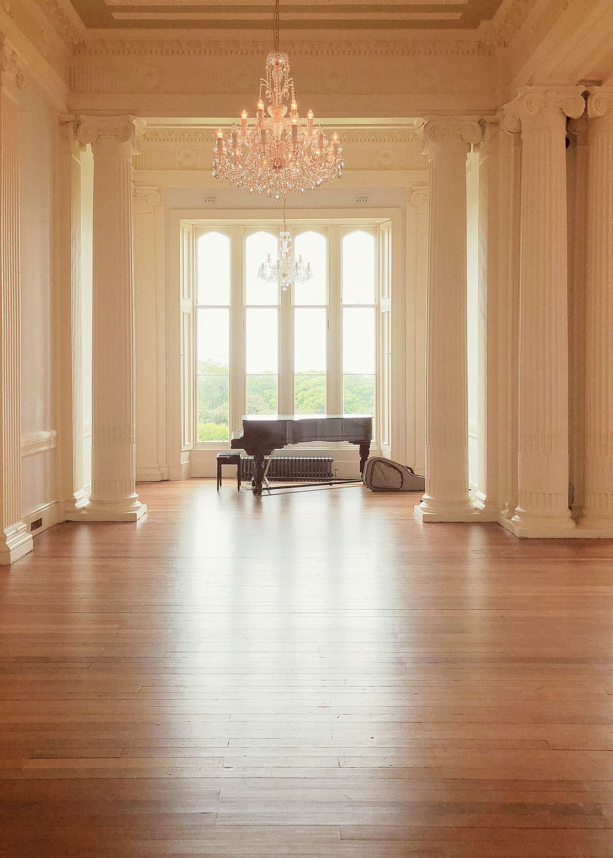 An empty ballrom in a private residence hold a grand piano and crystal chandelier.