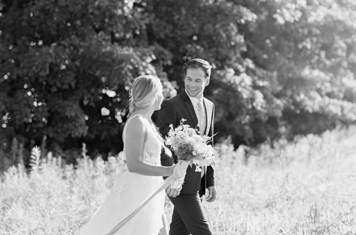 Bridal Portrait of Bride and Groom walking in sunlit field at Magnolia Hill Farm with Events Held Dear | Wedding Photographer | Anna Laero