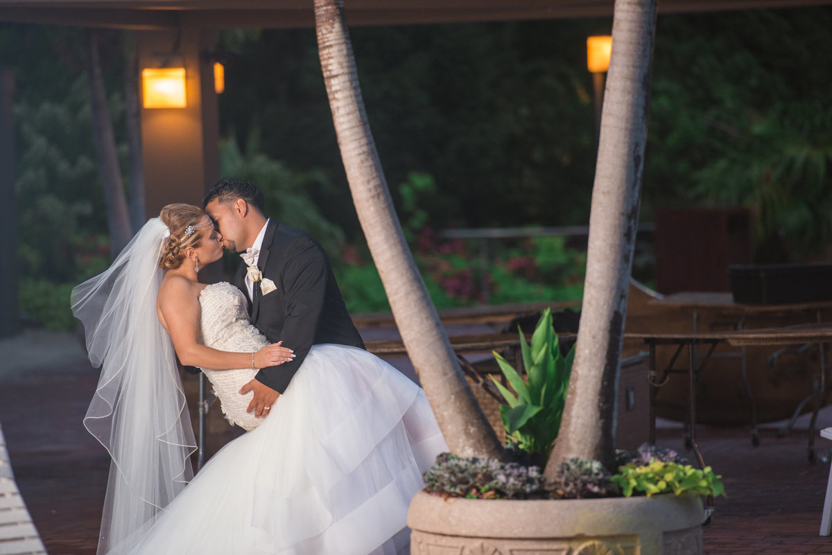 Bride and groom kissing by the palm trees at Crest Hollow Country Club