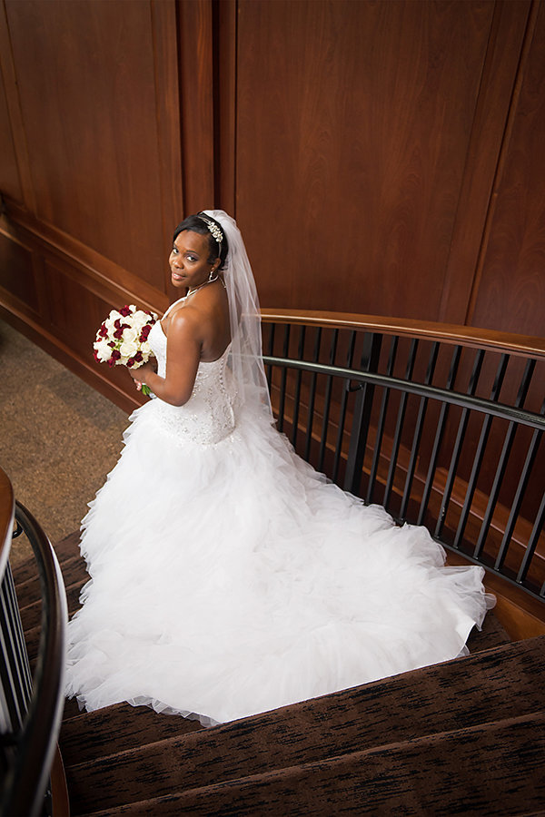 A photo of a bride on the staircase looking back over her shoulder