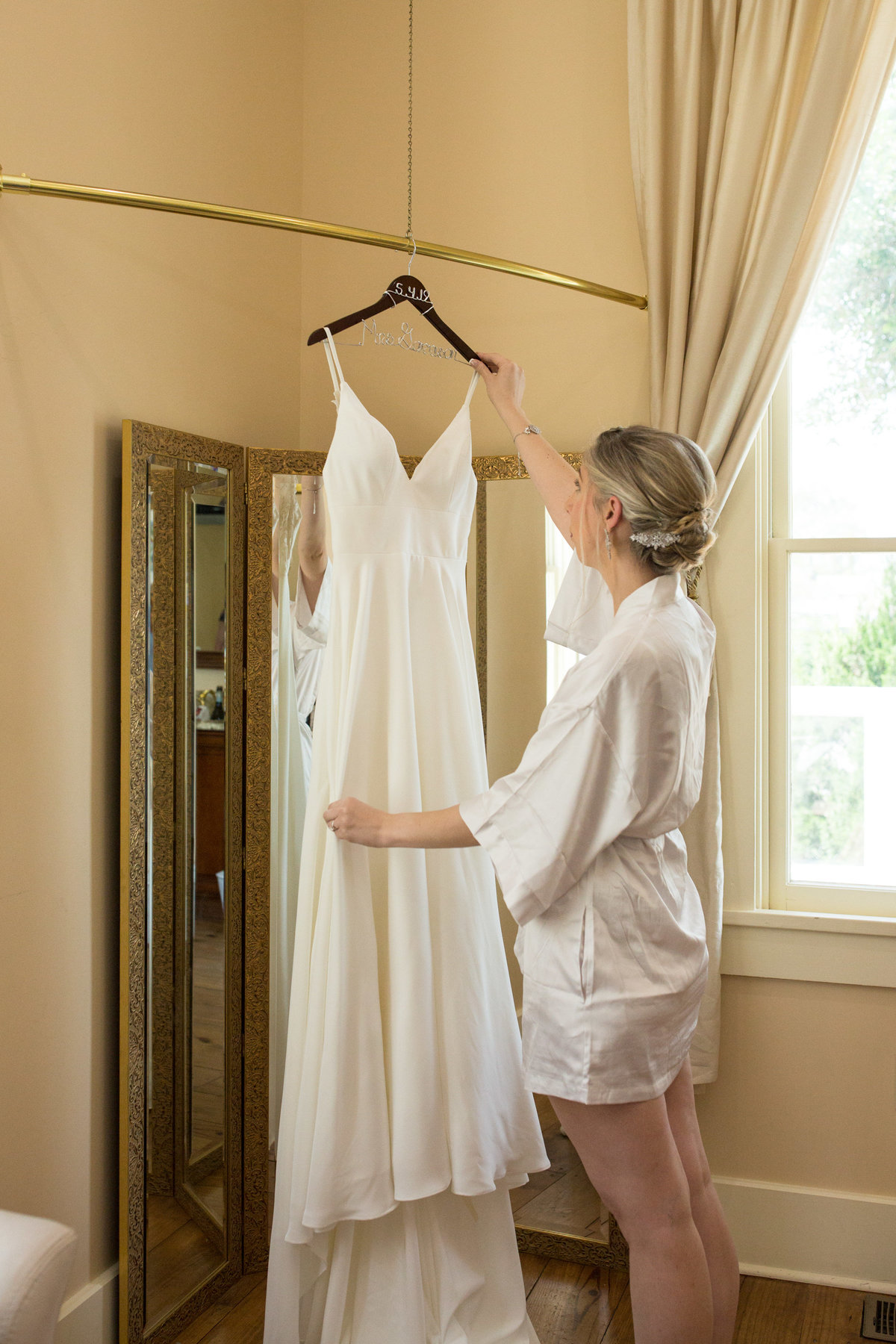 bride holding up her dress in her robe when she is about to get dressed