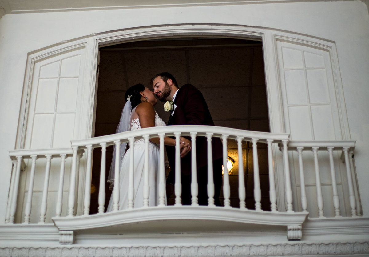 Bride and groom about to kiss on balcony at George Washington Hotel