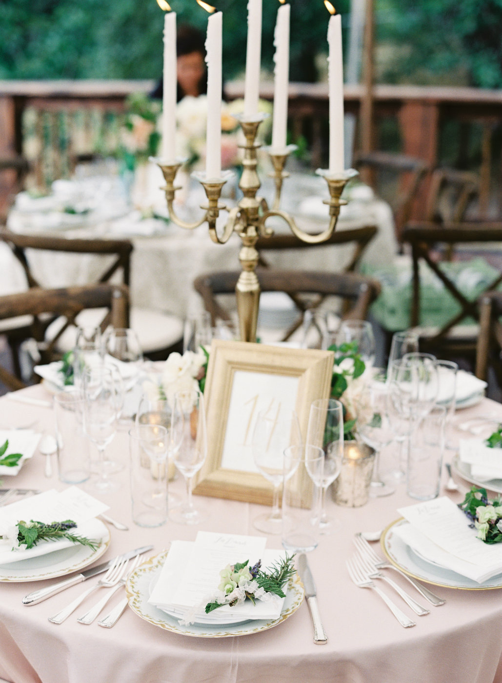 Luxury tent wedding tablescape with gold candelabra and hand tied posies at each place setting.