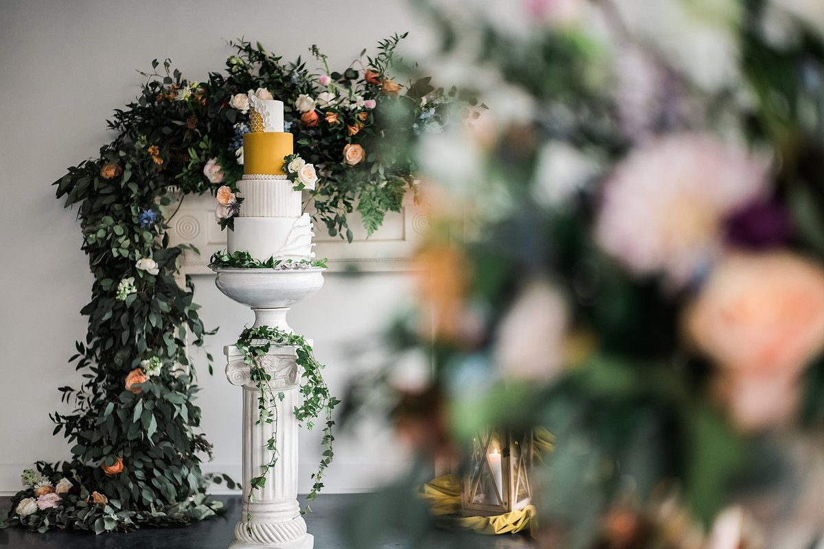A mantel, column, and lantern decorated with florals and cake.