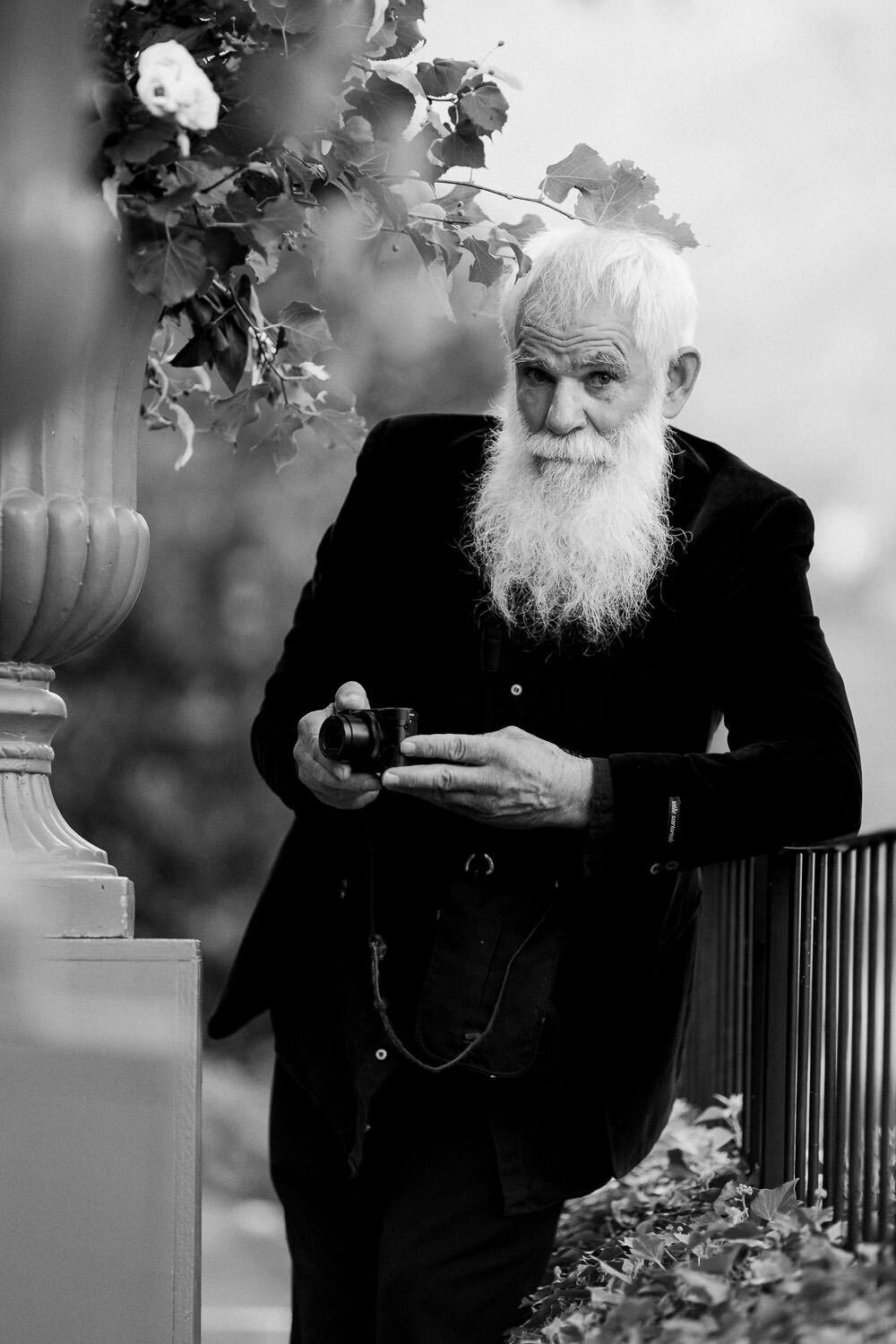 white bearded old man holding camera leaning against fence in black suit