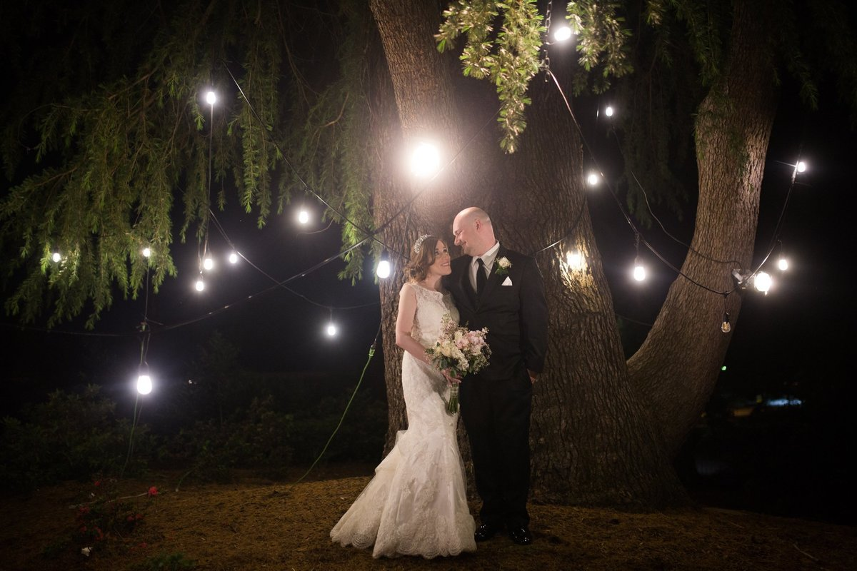 Wedding Photographer, bride and groom standing under lights at night