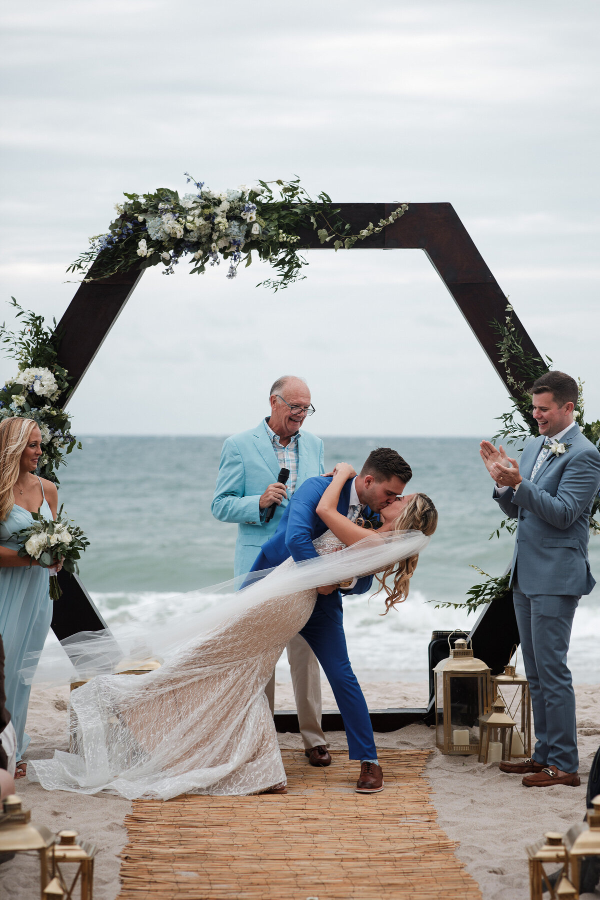 Groom dips his bride in epic first kiss in front of a hexagon wedding arch on the beach