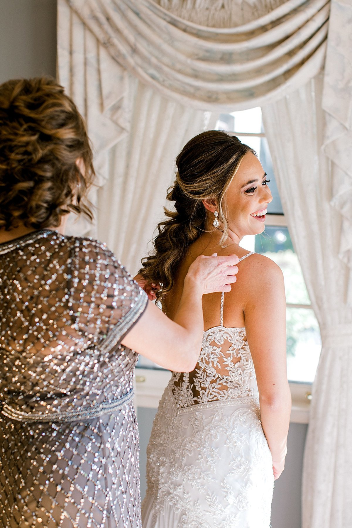 mother of bride getting bride into wedding dress