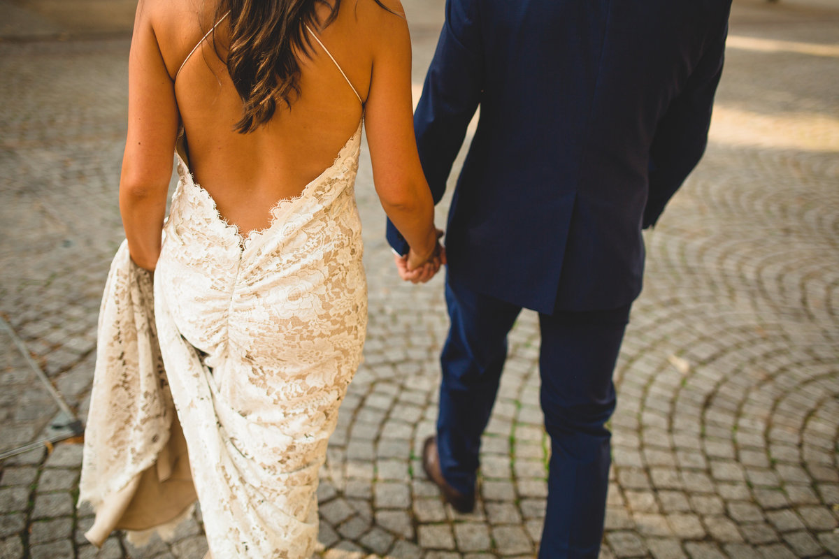bride and groom holding hands on cobbles