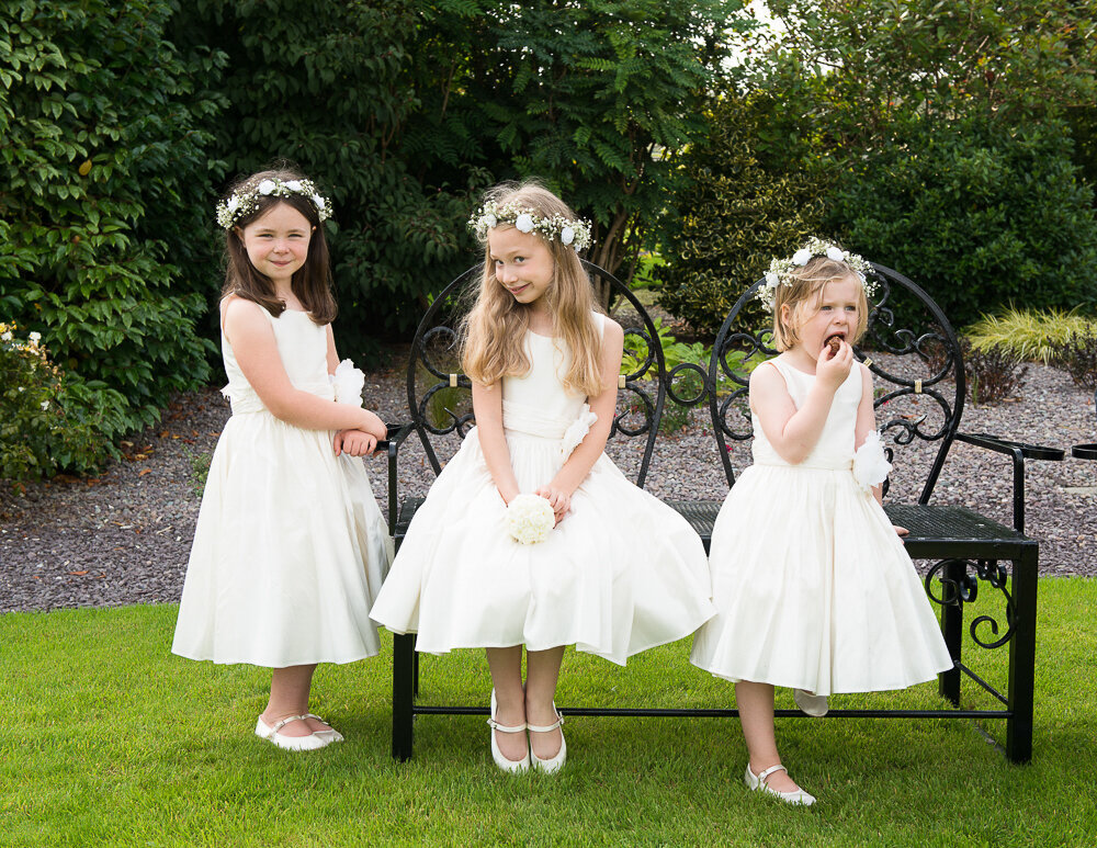 three flower girls sitting on a garden bench wearing white dresses and white flower head pieces