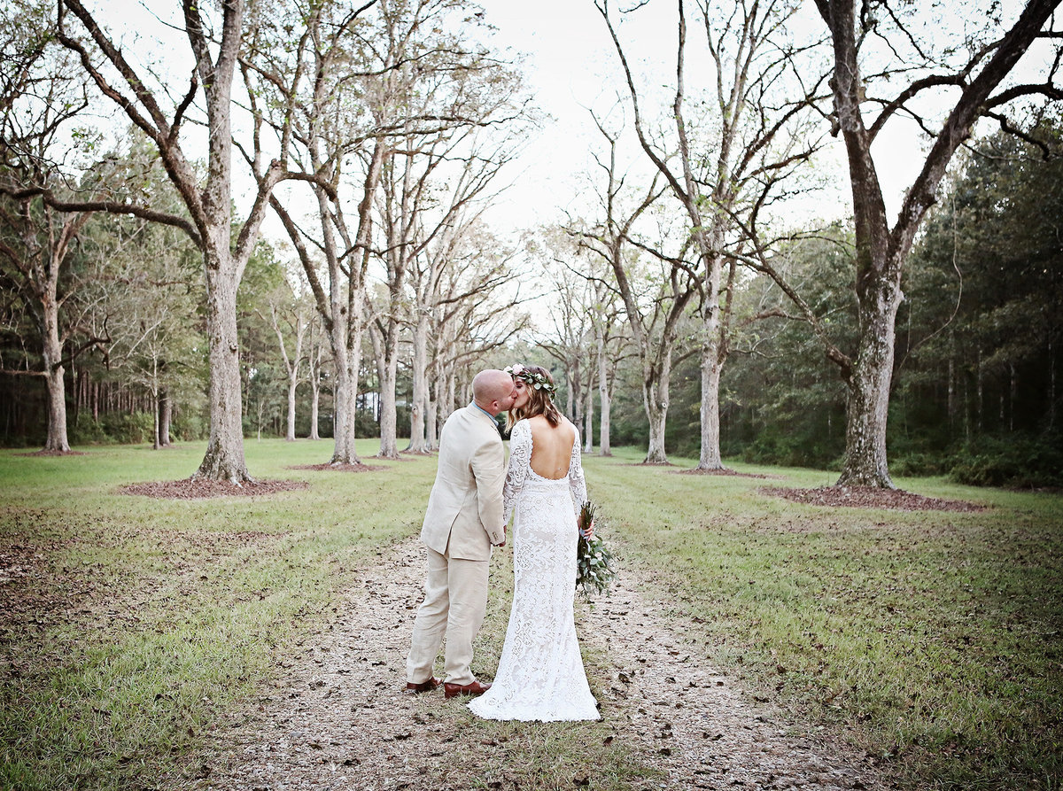 bride and groom kissing on tree lined drive in Ethel, Louisiana