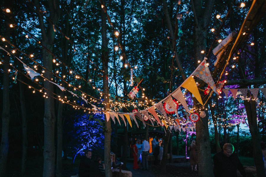 night photography of fairy lights and bunting at tipi wedding