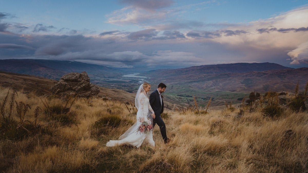 bride and groom walking through golden grass in the hills of bannockburn