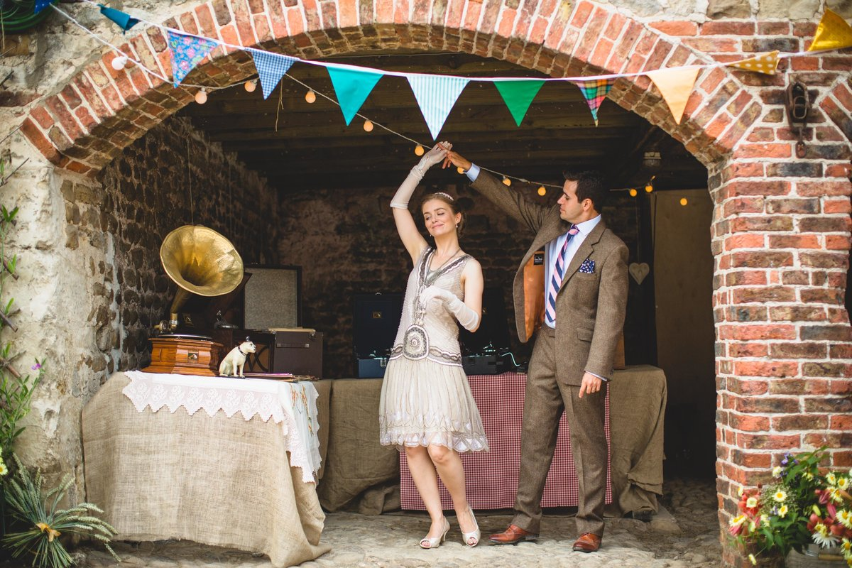 a bride and groom are dancing to a vintage hmv gramophone beneath bunting at their yorkshire wedding