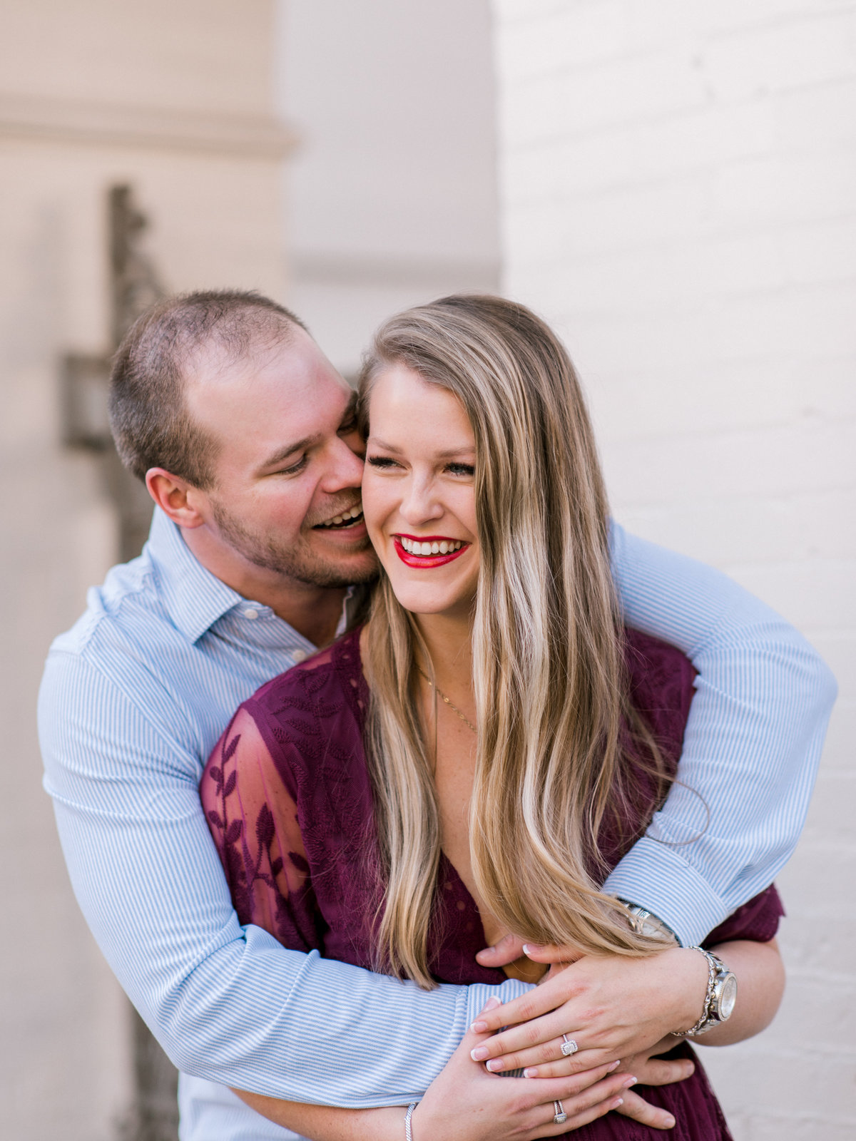 Guy hugs girl during engagement session in Johnson Square Savannah