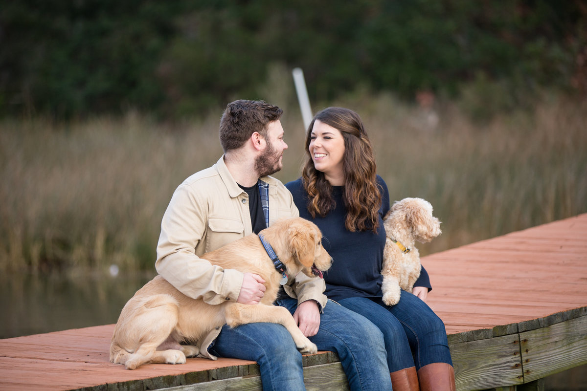 couple sitting on a dock with their puppies during their engagement session