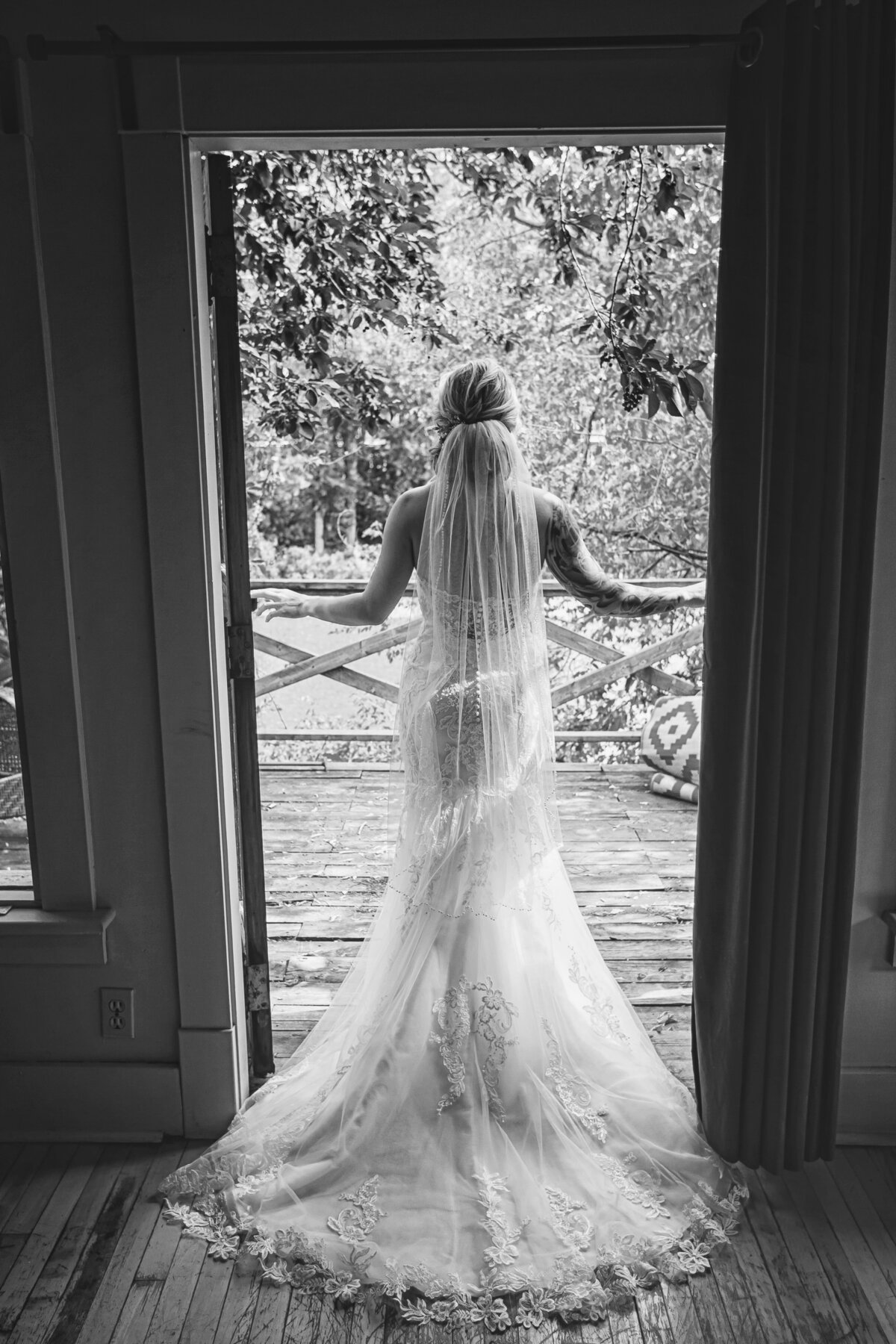 Stunning black and white image of bride in doorway. Long, lace veil trails over white, fitted gown.