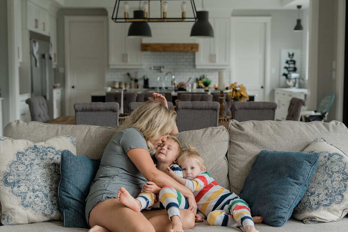 mother playing with children on the couch