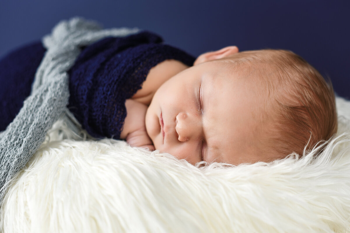 Beautiful Mississippi Newborn Photography: baby boy wrapped in navy sleeping