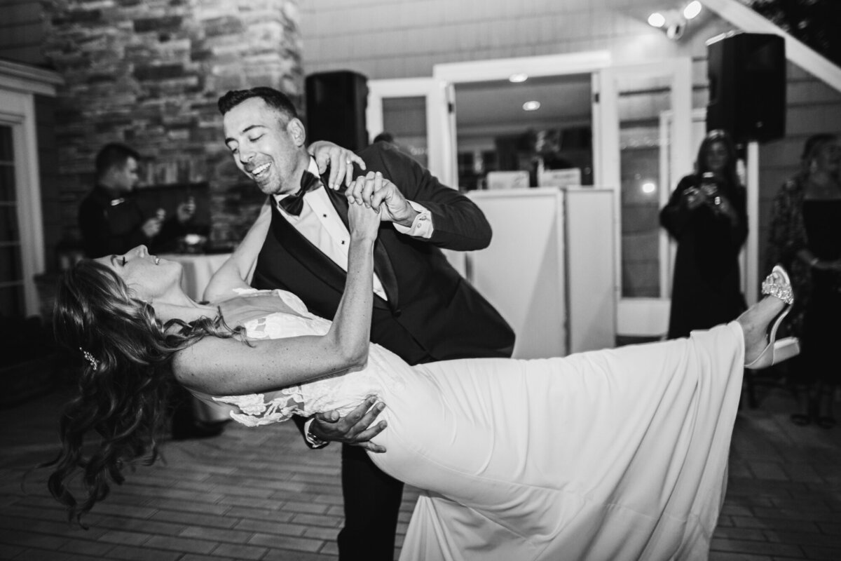 Grooms dips bride during dance