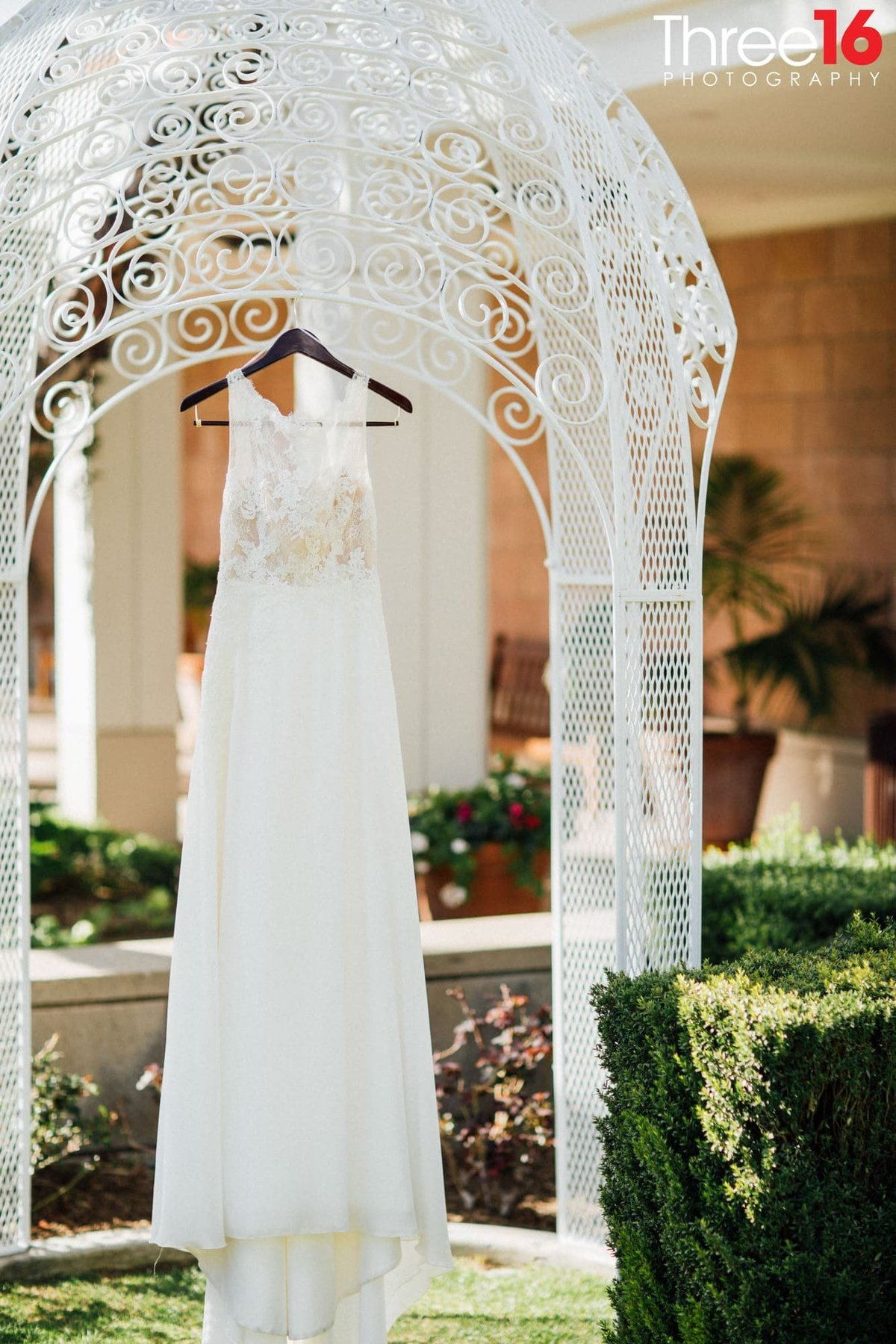 Bride's dress hangs from a small gazebo